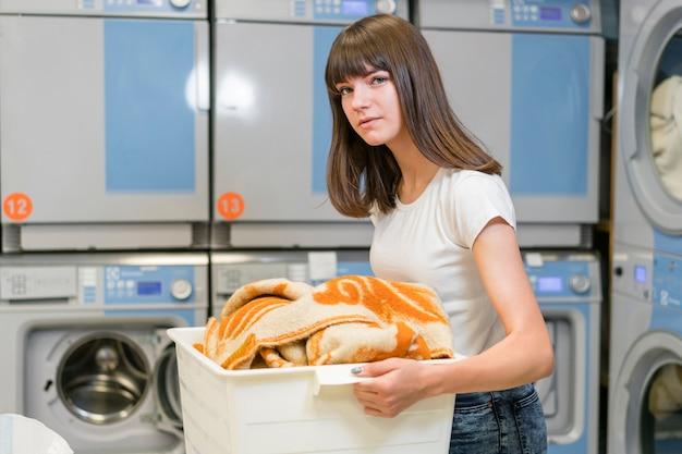 Cute woman holding heavy laundry box