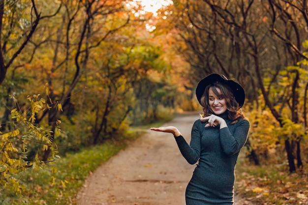 Милая женщина в черной шляпе и темном платье стоит в парке осенью на фоне тропинки