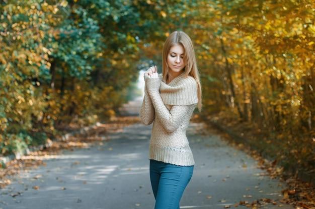 秋の公園に立っているジャージのかわいい女性