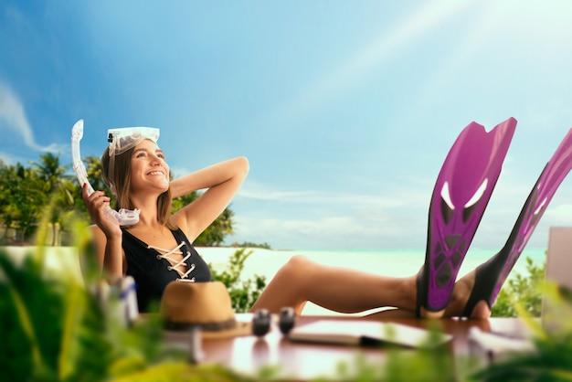 Милая женщина в купальнике и в ластах за столом, пальмами, океаном и райским островом