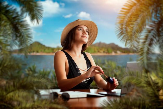 Милая женщина в купальнике и соломенной шляпе за столом