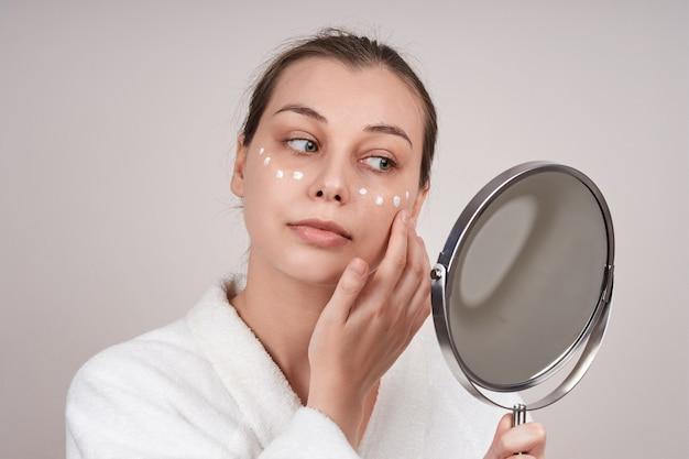 흰 가운을 입은 귀여운 여자가 거울을 보면서 얼굴에 크림을 바릅니다. 가벼운 벽.
