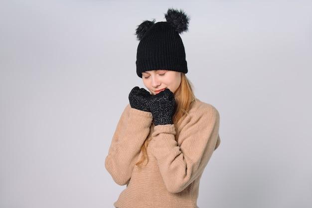 Милая женщина в зимней шапке и перчатках позирует с закрытыми глазами