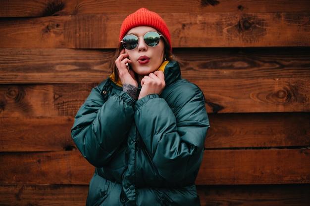 明るい冬の服装のかわいい女性が電話で話します