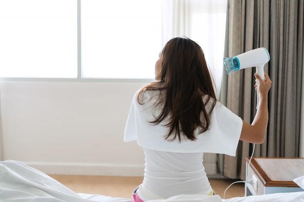 Милая женщина в пижаме сидит на кровати и сушит волосы утром