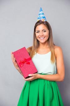 Милая женщина в шляпе партии держит подарочную коробку