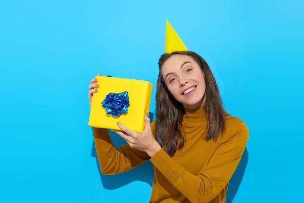 스튜디오에서 노란색 선물 상자를 들고 파티 모자에 귀여운 여자
