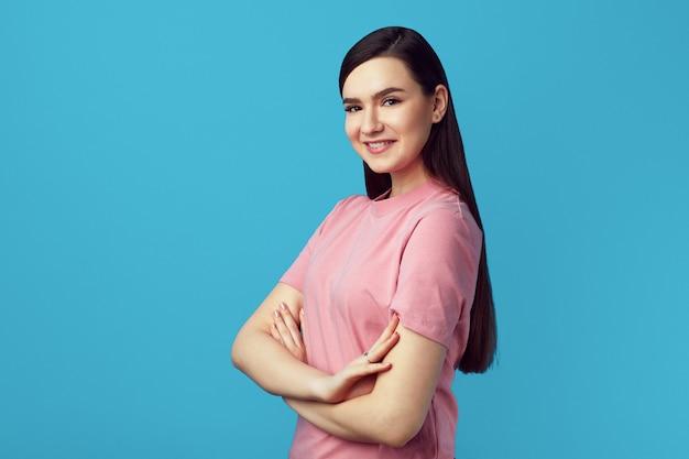 Милая женщина в розовой футболке улыбается и стоит со скрещенными руками на синем