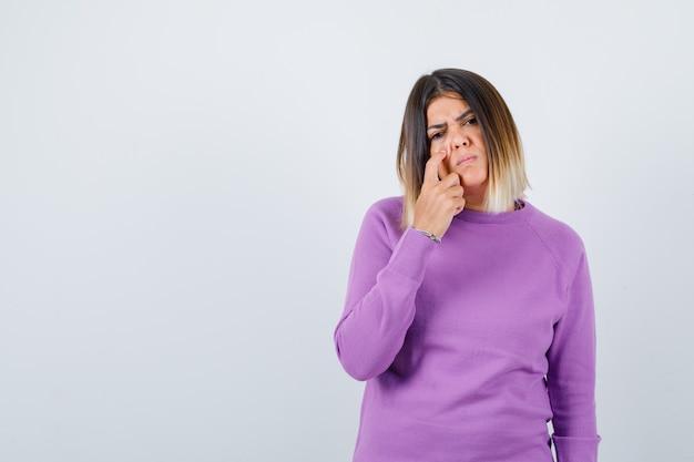 頬に指を保持し、暗い、正面図を見て紫色のセーターのかわいい女性。