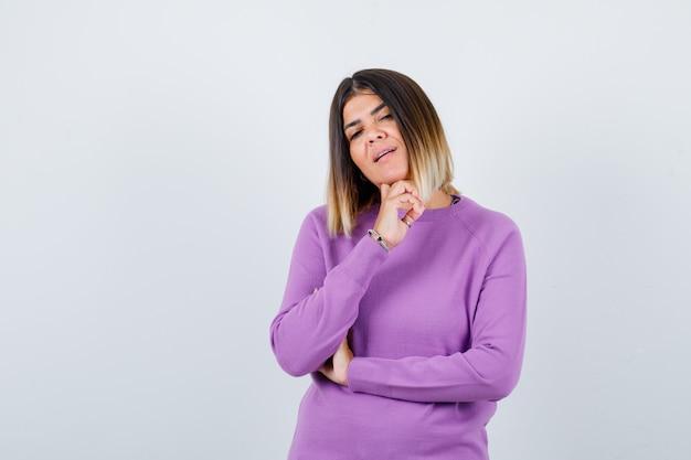 手にあごを支え、賢明な、正面図を探している紫色のセーターのかわいい女性。