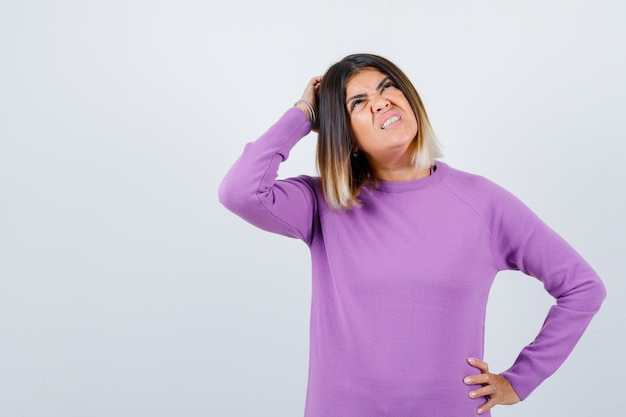 紫色のセーターで頭を掻く、見上げると忘れっぽい、正面のかわいい女性。