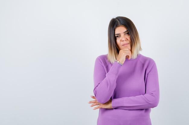 보라색 스웨터를 입은 귀여운 여자가 턱에 손을 대고 생각에 잠긴 앞모습을 보고 있습니다.