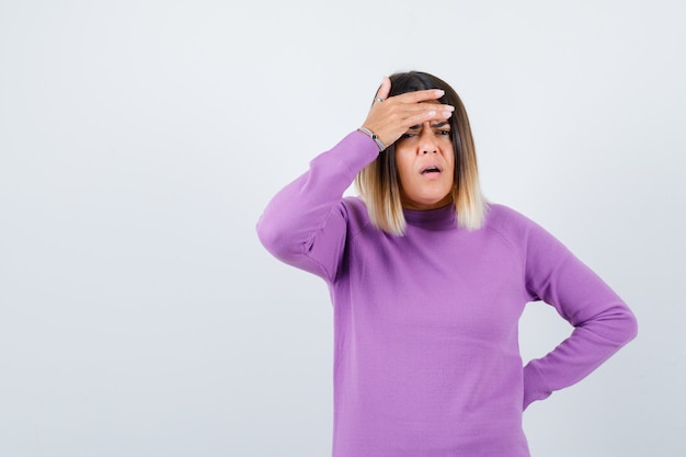 보라색 스웨터를 입은 귀여운 여성이 이마에 손을 대고 우울한 표정을 짓고 있습니다.