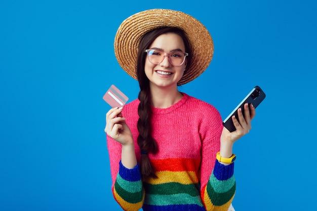 Милая женщина в радужном свитере держит пластиковую кредитную карту и смартфон