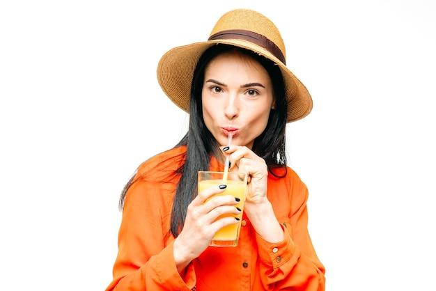 シャツと麦わら帽子のかわいい女性は、白に絞りたてのオレンジジュースを飲みます。