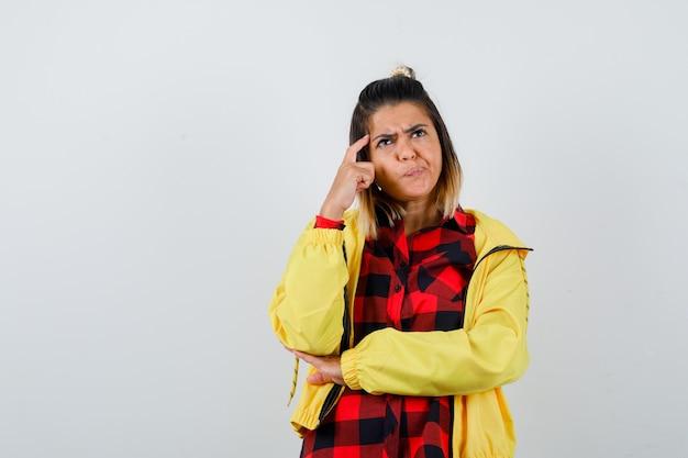 Милая женщина в рубашке, куртке, держащей палец на висках, глядя вверх и задумчиво, вид спереди.