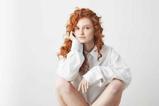 白い壁の上に座ってカメラを見て笑顔のシャツでかわいい女性