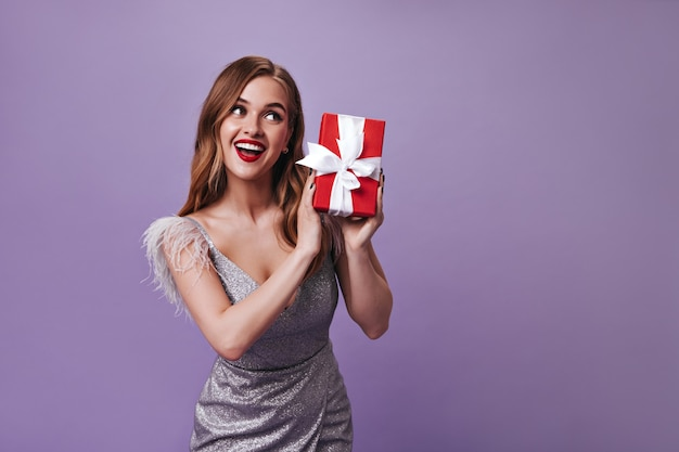 Милая женщина в серебряном платье держит подарок на фиолетовой стене