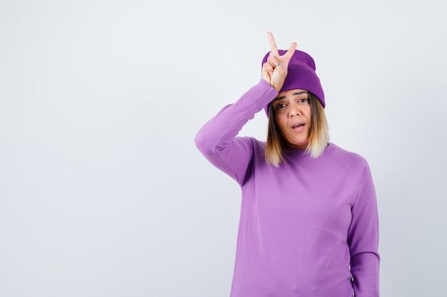 セーターを着たかわいい女性、平和のジェスチャーを示し、不思議に見えるビーニー、正面図。