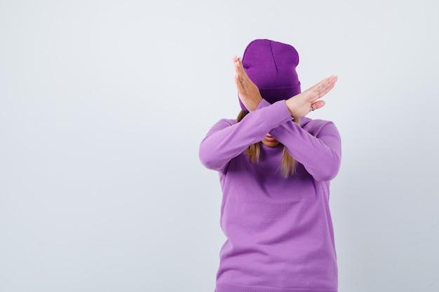セーターを着たかわいい女性、拒否ジェスチャーを示し、毅然とした表情をしているビーニー、正面図。