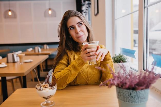 카푸치노 한잔과 함께 카페에서 쉬고있는 동안 뭔가에 대해 생각하는 유행 노란색 스웨터에 귀여운 여자. 친구를 기다리고 아이스크림을 즐기는 멋진 아가씨의 실내 초상화.