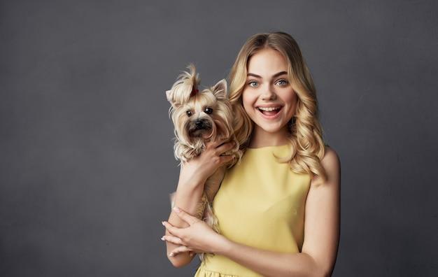 Милая женщина в желтом платье с маленькой породистой собакой дружба домашнее животное радость