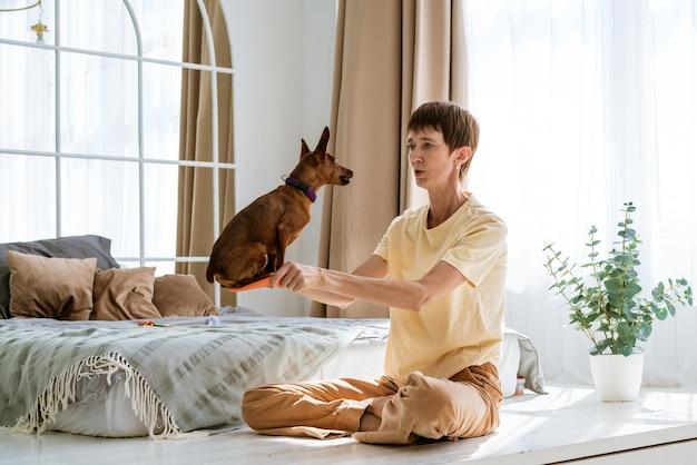 かわいい女性は床に座っている間自宅で彼女の犬を訓練しています白人の女の子は動物のトリックを教えています...