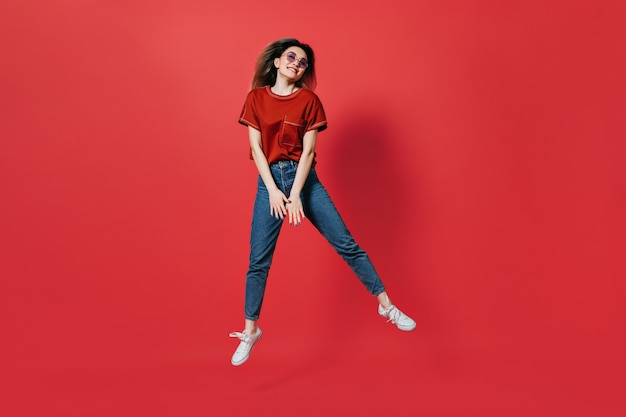 Cute woman in jeans and bright t-shirt jumping on red wall