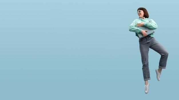 Salto sveglio della donna isolato sull'azzurro con lo spazio della copia