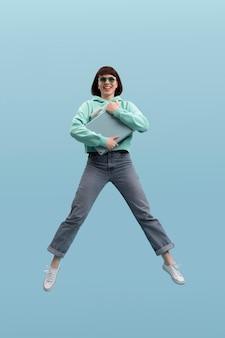 Милая женщина прыгает изолированной на синем