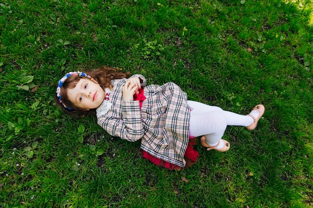 A cute woman lays on a green grass in a beautiful dress
