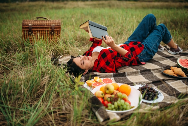 Cute woman lies on plaid and reads book, picnic on meadow. romantic junket, happy holiday