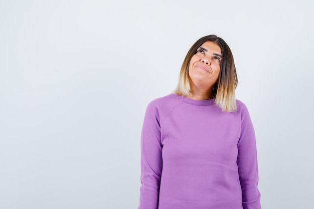 Cute woman looking up in purple sweater and looking dreamy , front view.
