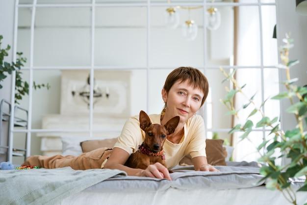 彼女の最愛の犬と一緒にベッドでリラックスして彼女の胃の上に横たわっているかわいい女性は、暖かい快適さで朝の愛撫...