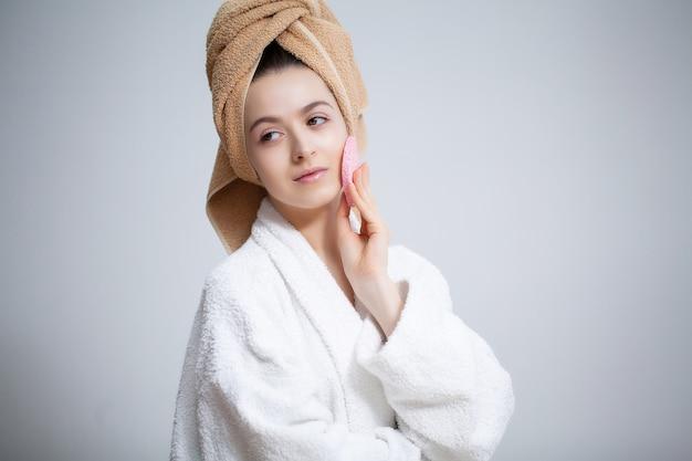 かわいい女性がトイレで顔に化粧をします