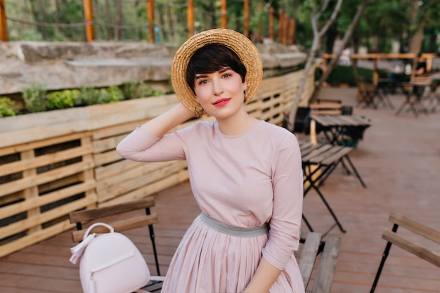 Cute woman in old-fashioned dress with trendy backpack gladly posing in outdoor cafe with tables