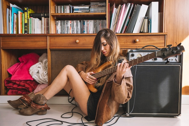 Cute woman playing guitar on floor