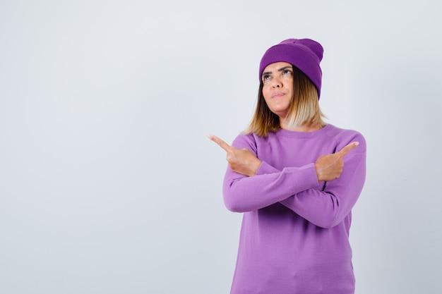 반대 방향을 가리키는 귀여운 여성, 스웨터, 비니를 입고 꿈꾸는 듯한 전면 전망.