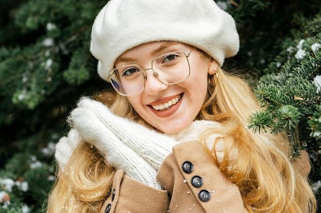 Милая женщина позирует в парке зимой