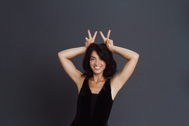 Cute woman posing over grey wall and make funny gesture