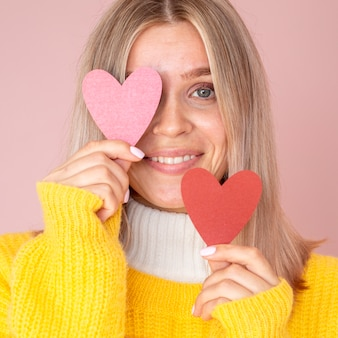Cute woman posing with paper hearts