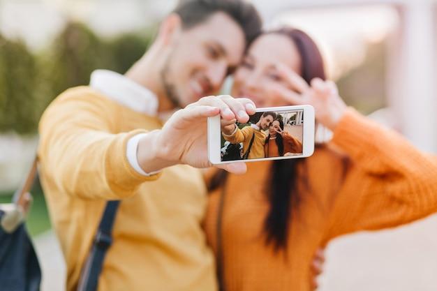 오렌지 스웨터에 그녀의 남자 친구가 셀카를 만드는 동안 평화 기호로 포즈를 취하는 귀여운 여자