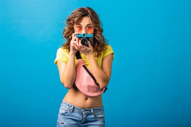 Donna carina in posa con la macchina fotografica d'epoca scattare foto vestita in abito colorato estate hipster isolato su sfondo blu, nascondendo l'espressione del viso sorpreso