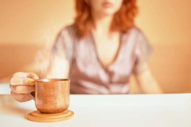 Cute woman in a purple silk robe drinking coffee early in the morning in bed