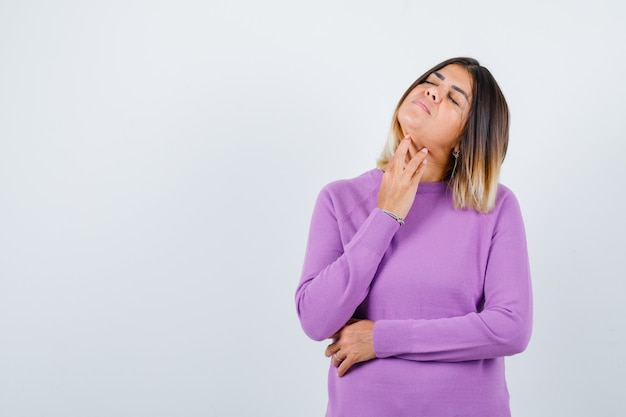 Donna carina in maglione viola che tocca la pelle sul collo, tiene gli occhi chiusi e sembra rilassata, vista frontale.