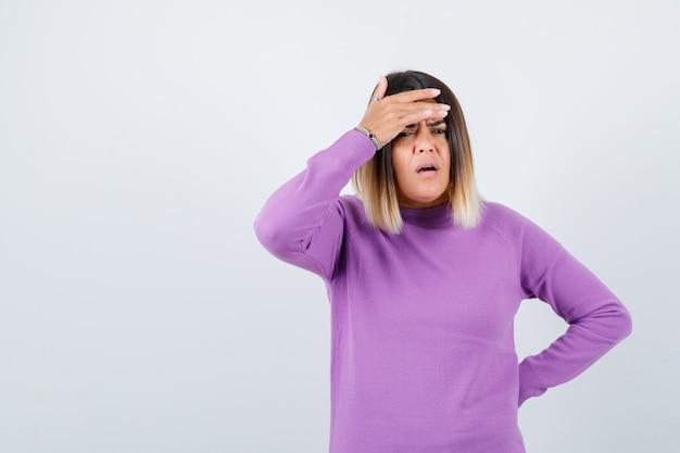 Donna carina in maglione viola con la mano sulla fronte e guardando giù, vista frontale.
