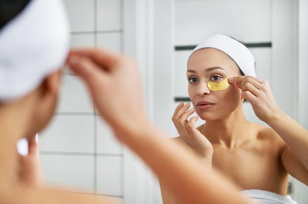 かわいい女性がバスルームの目の下にパッチを置きます。目の肌の美しさ