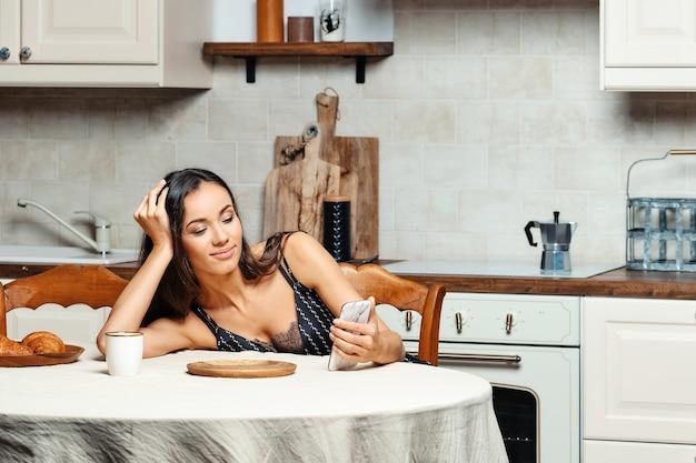 Милая женщина читает новости на смартфоне, ожидая заваривания кофе