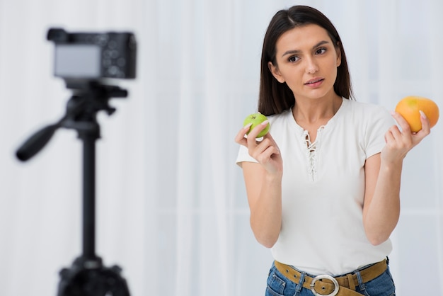 Cute woman recording with fruits