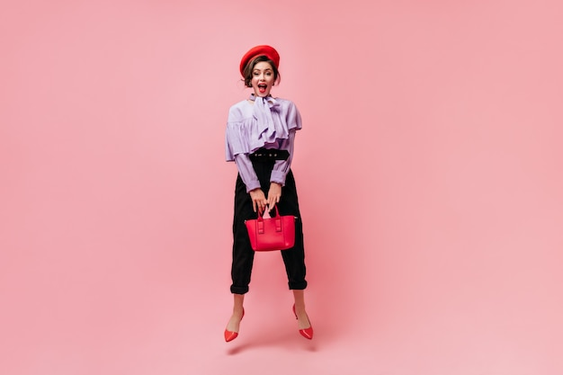 Cute woman in red beret is holding bag and jumping on pink background.